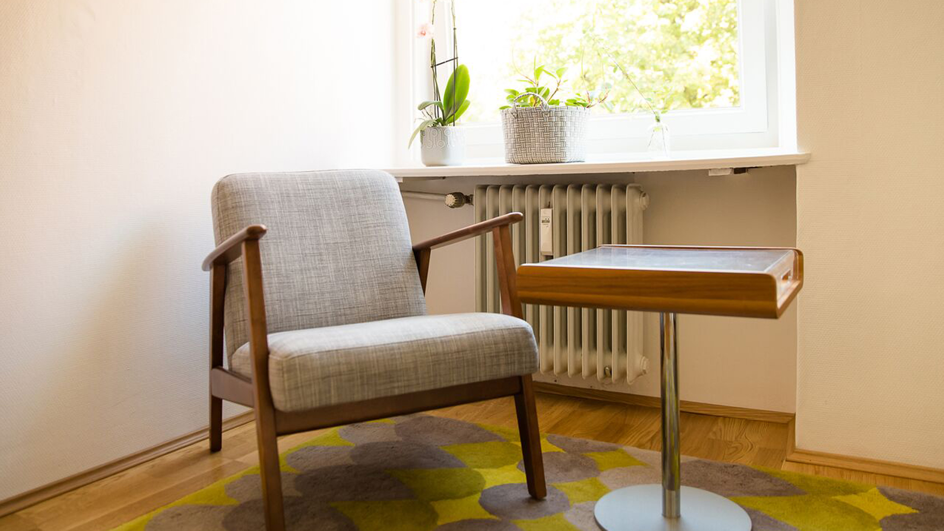 Ein Sessel und ein kleiner Stehtisch die direkt vor einer Fensterbank stehen